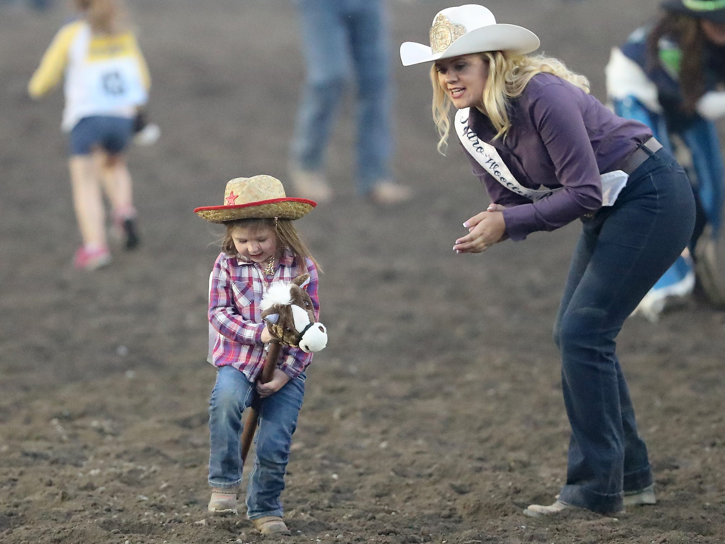 A youngster is cheered on by rodeo royalty during the stick horse race at the Kitsap County Fair & Stampede on Friday, August 24. 2018.