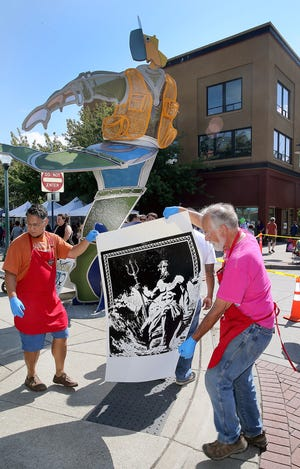 Wayzgoose Arts Festival volunteers Steve Ramstad, left, and Frank Carsey both of Bremerton move an inked steamroller printing of Poseidon  from artist Gretchen Lund of Port Orchard at Fourth Street and Pacific in downtown Bremerton on Saturday, September 1, 2018.