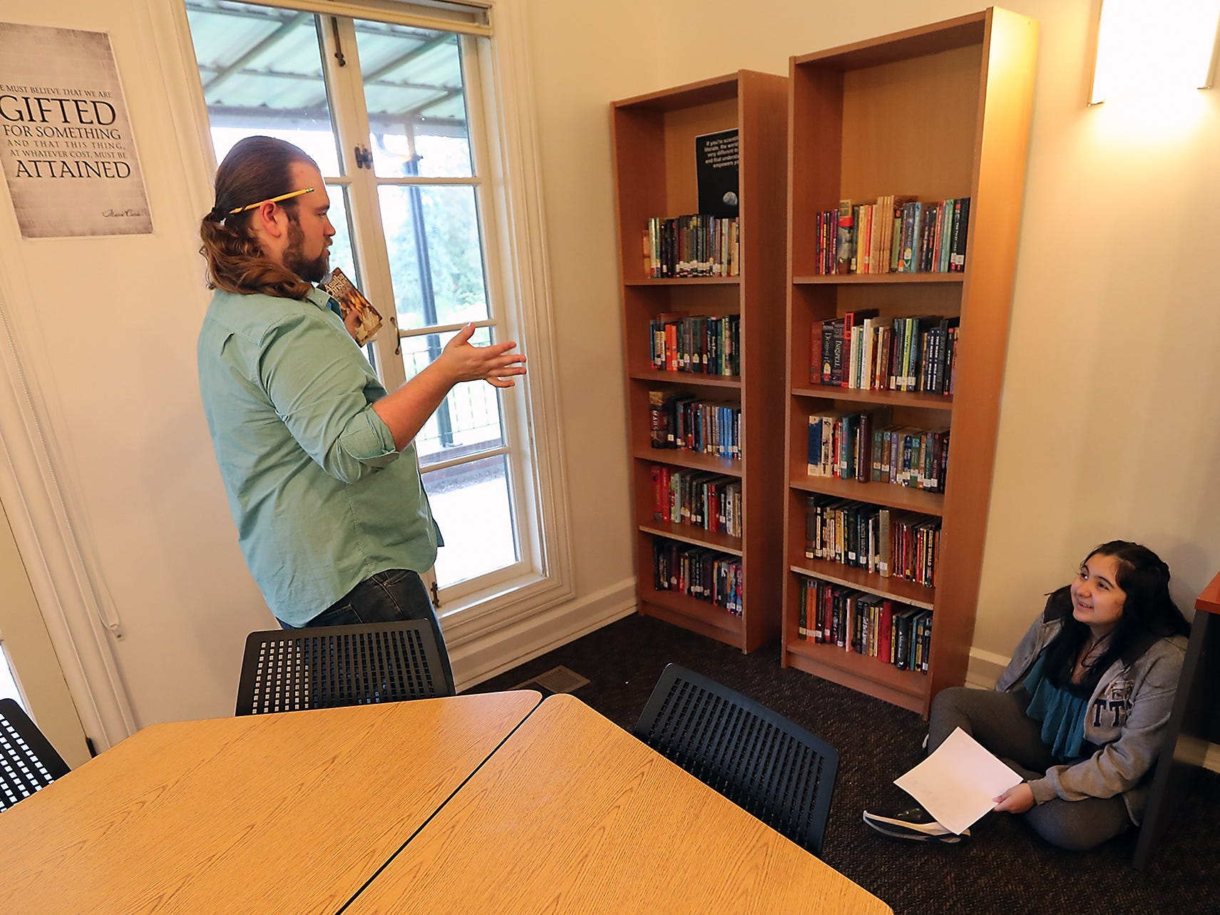 While looking over her class schedule, student Jewelian Lawrence, 14, chats with Language Arts teacher Hank Hayden as he organizes the bookshelves in his classroom during the Chief Kitsap Academy open house at their new campus in Poulsbo on Thursday, August 30, 2018.