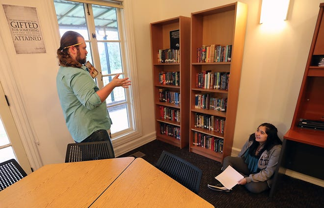 Jewelian Lawrence, 14, checks out her new classroom and chats with language arts teacher Hank Hayden during an open house for the new Chief Kitsap Academy campus near Poulsbo on Aug. 30. The Suquamish Tribe's school is moving this year to the site formerly occupied by the Northwest College of Art & Design.