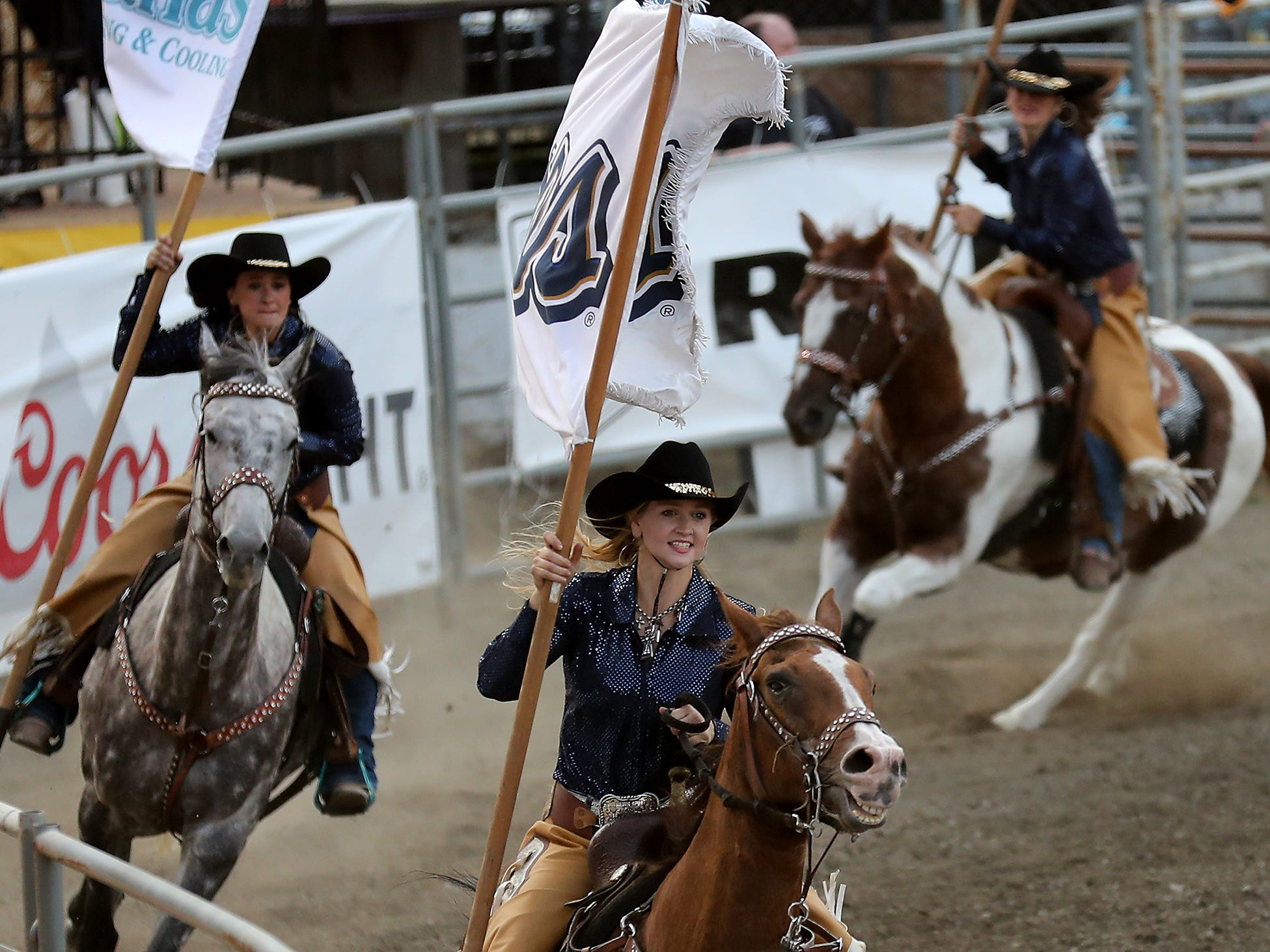 Kitsap Stampede Starlet Serenity Frank (front) carries a sponsor flag through the arena at the Kitsap County Fair & Stampede on Thursday, August 23. 2018.