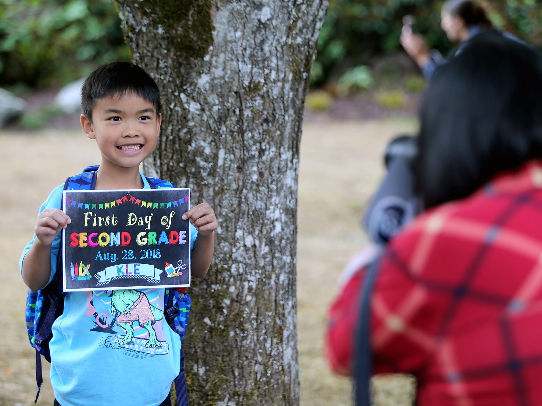 Jayden Aguilar, 7, gets his photo taken by his mom Daisy on the first day of school at Kitsap Lake Elementary School on Wednesday, August 29, 2018.