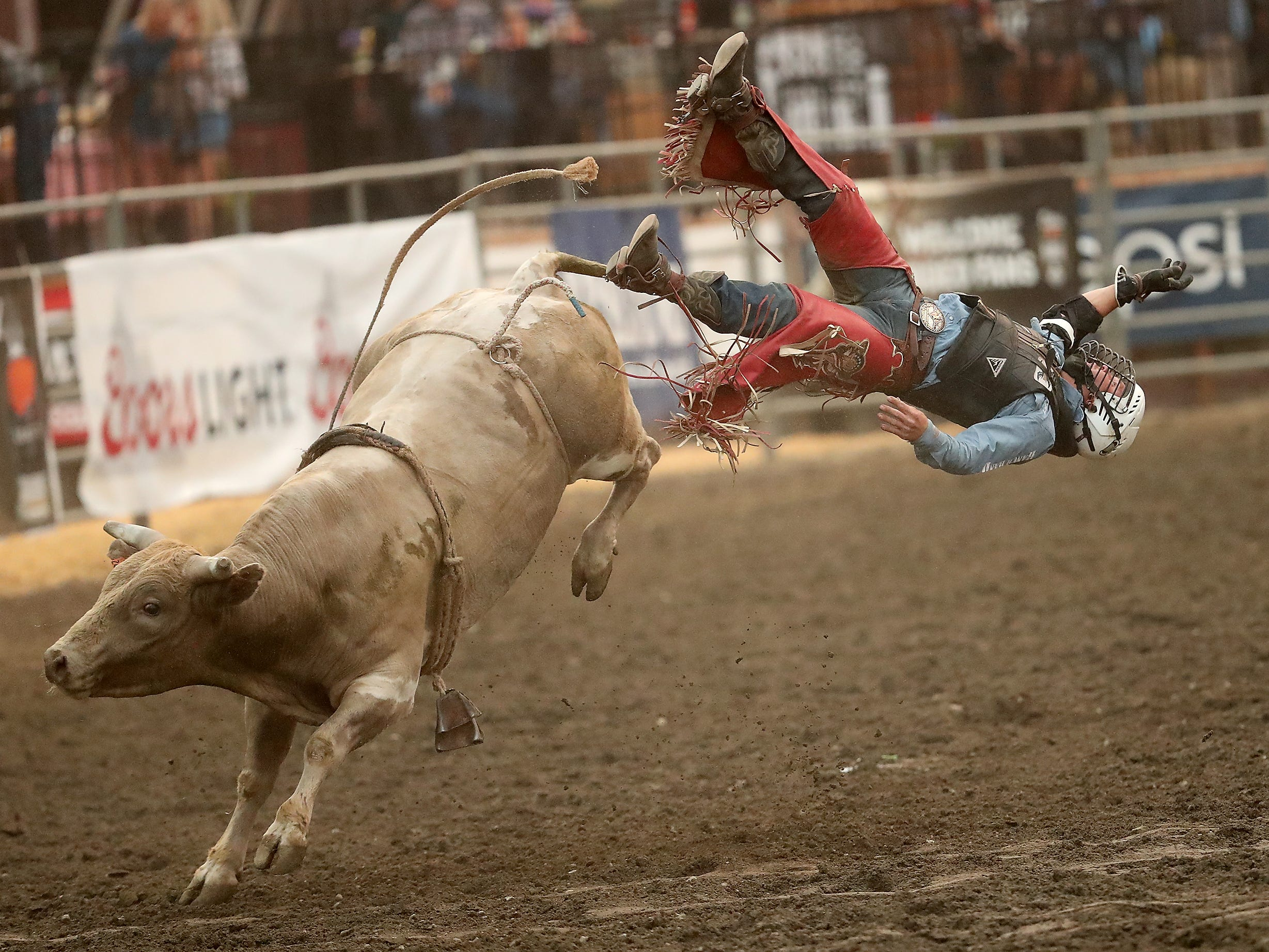 Bull rider Trey Benton III, of Rock Island, Texas, soars through the air off the back of a bull named Single Wide during the PRCA Xtreme Bulls at the Kitsap County Fair & Stampede in Silverdale, Washington on Wednesday, August 22. 2018.