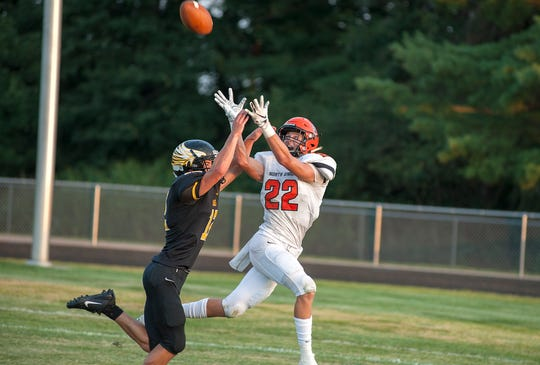 North Union's Preston Crabtree attempts a catch as Colonel Crawford's Keton Pfeifer defends.