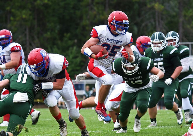Hartford's Zachary Burek busts through a hole during the Hurricanes' 35-33 win over defending champion St. Johnsbury Academy in the Vermont high school football season opener at Fairbanks Field on Saturday, Sept. 1, 2018. It was a rematch of last season's state final.