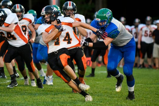 Colchester's Conroy Odonnell (61) grabs the shirt of Middlebury's Tyler Buxton (14) for the tackle during the boys high school football game between Middlebury and Colchester at Colchester high school on Friday night August 31, 2018 in Colchester.