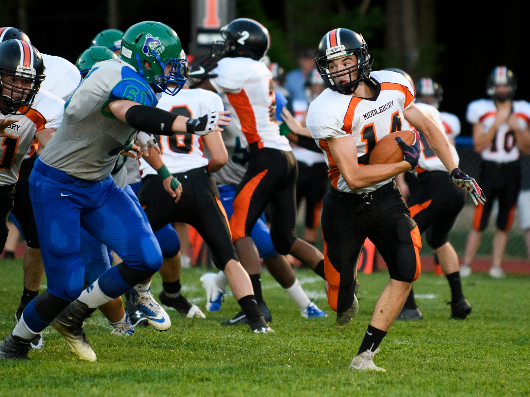 Middlebury's Tyler Buxton (14) runs with the football during the boys high school football game between Middlebury and Colchester at Colchester high school on Friday night August 31, 2018 in Colchester.