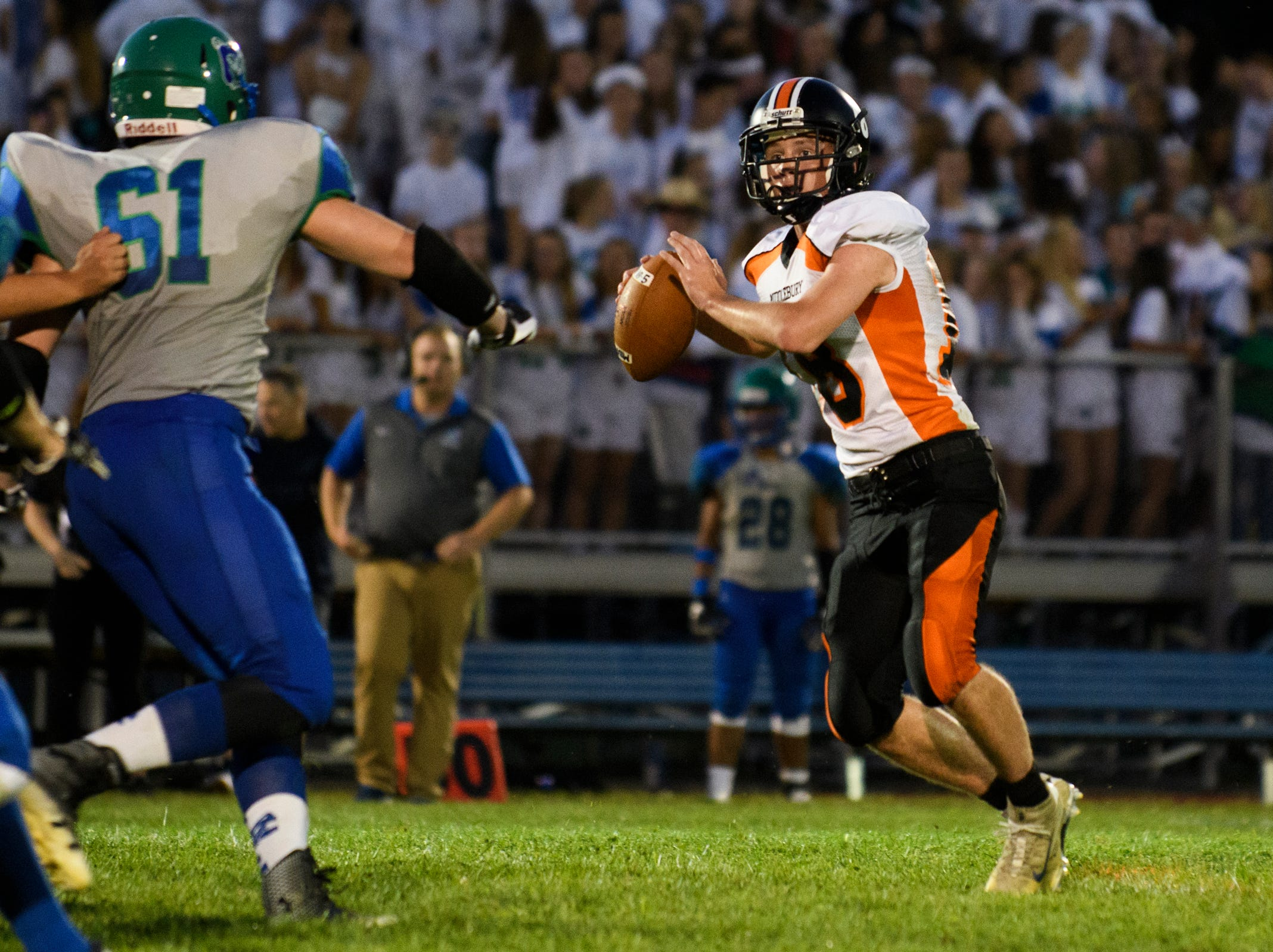 Middlebury quarterback Tim Goettelmann (18) looks to pass the ball during the boys high school football game between Middlebury and Colchester at Colchester high school on Friday night August 31, 2018 in Colchester.