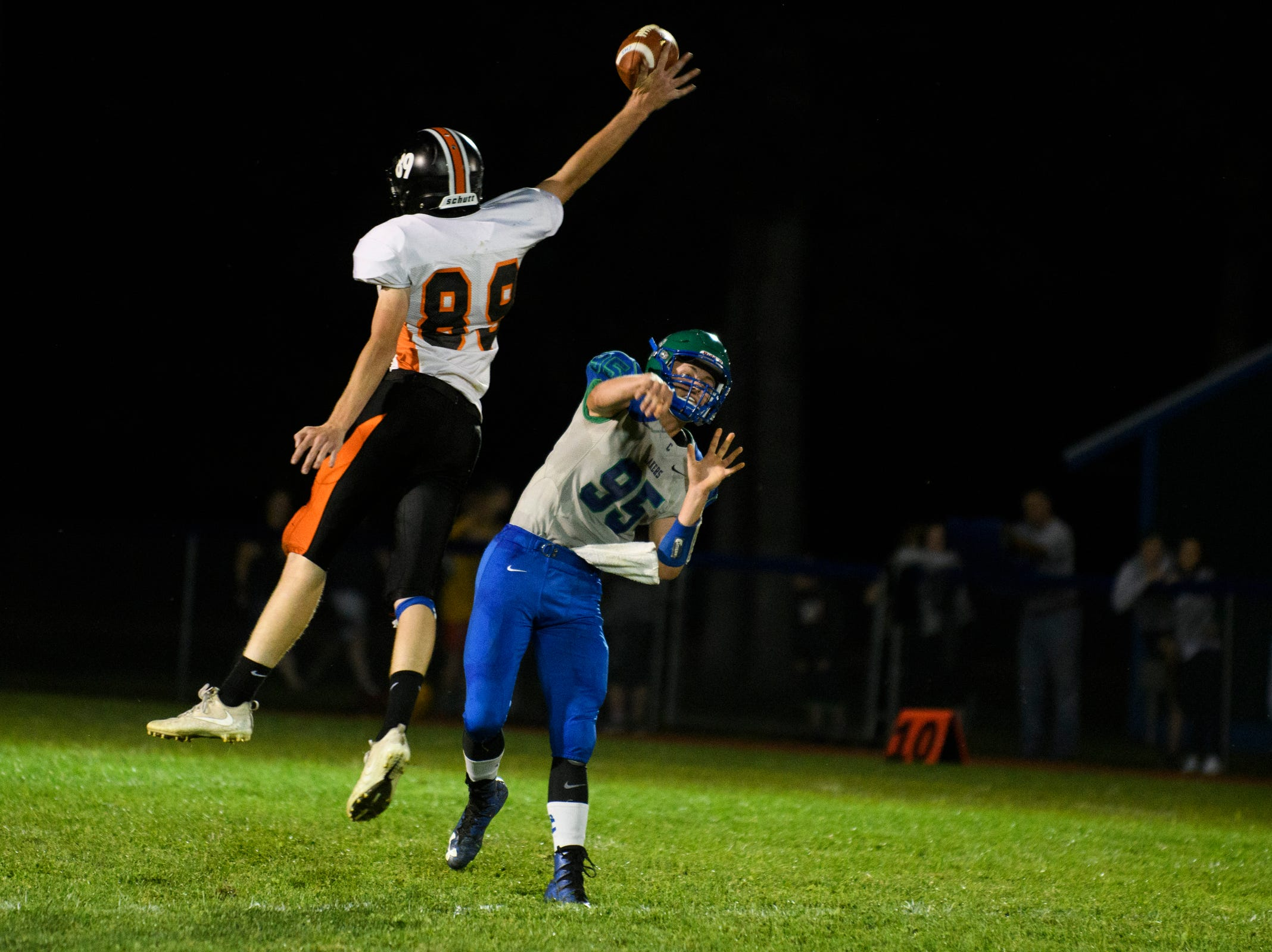Middlebury's Wyatt Cameron (89) blocks the pass by Colchester quarterback LLewey Powell (95) during the boys high school football game between Middlebury and Colchester at Colchester high school on Friday night August 31, 2018 in Colchester.