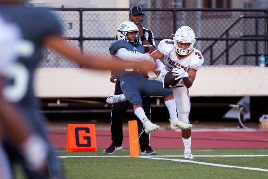 Beeville Trojans' Donyvan Givens scores a touchdown as King Mustangs' Javier Guy can't break up the play in the first quarter of the game at Buccaneer Stadium on Friday, August 31, 2018.