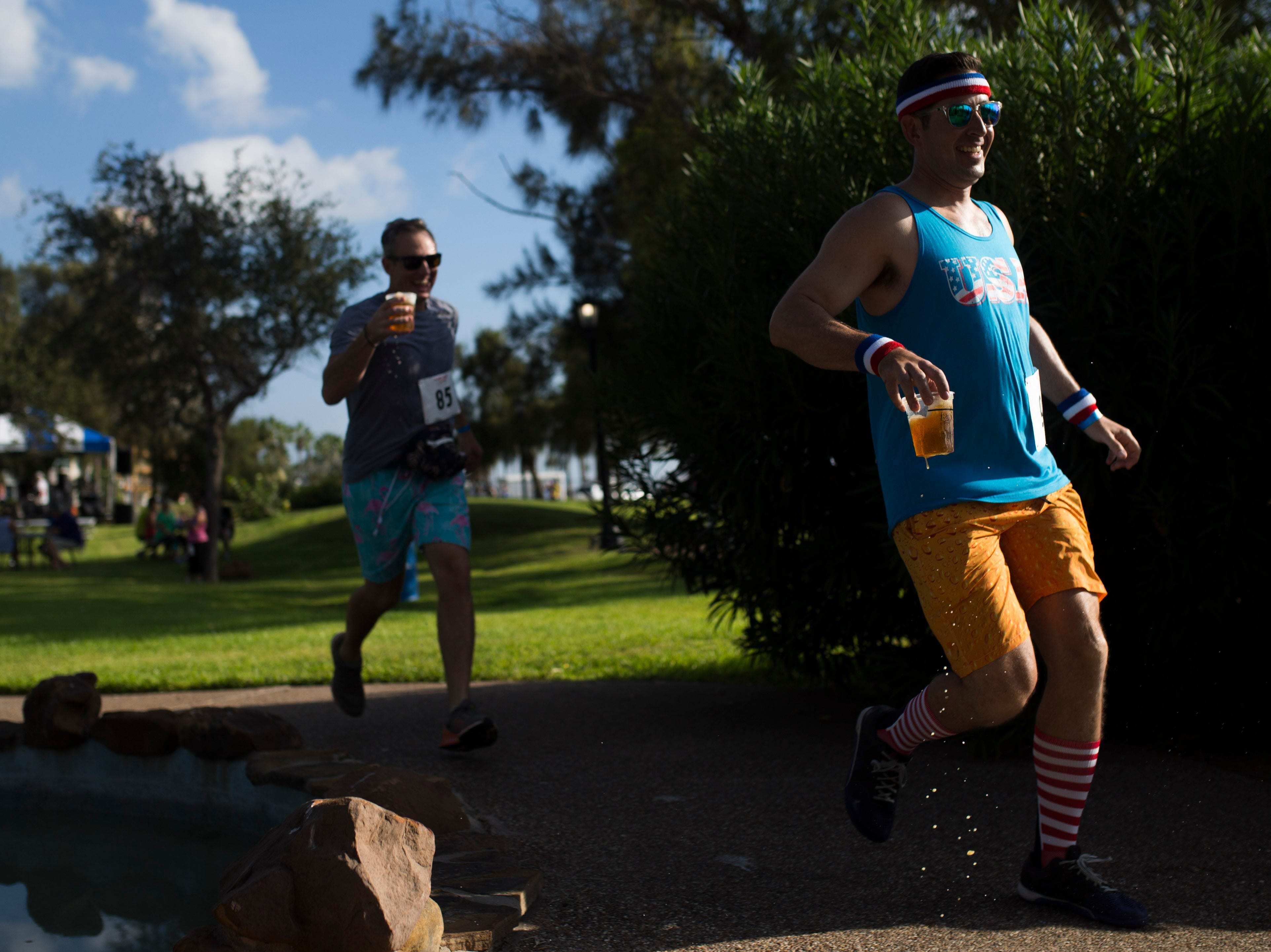 John Kollar, 40, finishes the 1/2 K By the Bay Beer Run during the annual Arts Alive Festival at the Art Center of Corpus Christi on Saturday, Sep. 1, 2018.