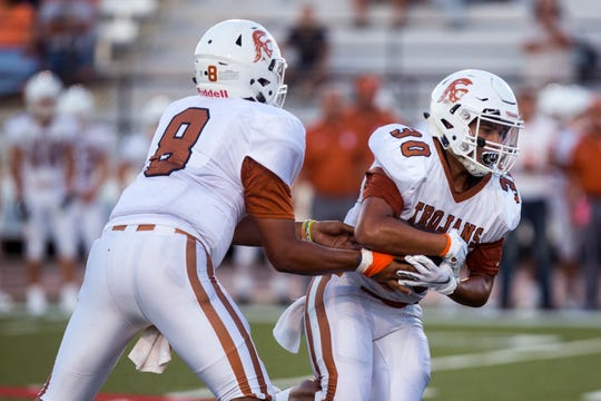Beeville Trojans quarterback Seth Gomez hands off to Devn Palacios in the first quarter of the game against the King Mustangs at Buccaneer Stadium on Friday, August 31, 2018.