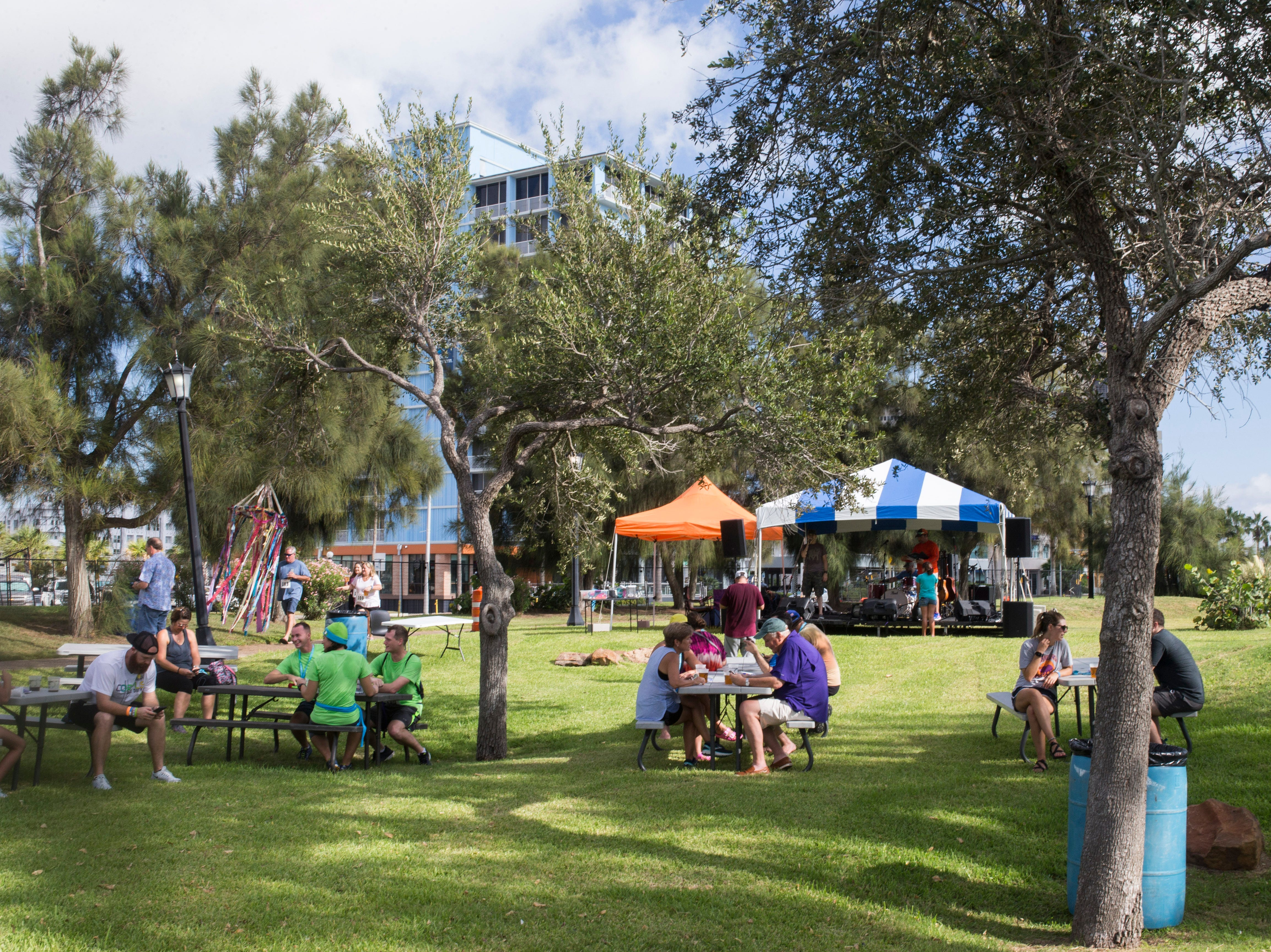 People sit in the shade and listen to music during the annual Arts Alive Festival at the Art Center of Corpus Christi on Saturday, Sep. 1, 2018.