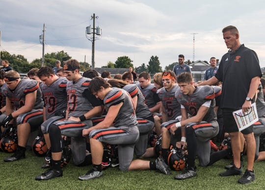 The Waverly football team takes a moment of silence before they break through a banner that honors JeRicho Rohn at their home game versus Zane Trace Friday night.