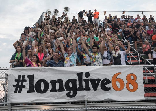 The Waverly student section dons the banner #longlive68 in remembrance of JeRicho Rohn as they celebrate the Tigers scoring during a football game against Zane Trace Friday night.