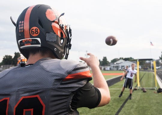 Along with the rest of the Waverly football team, quarterback Haydn' Shanks, left, wears the number 68 in honor of his former teammate JeRicho Rohn as he practices throwing a football before the game against Zane Trace on Friday, August 31, 2018.