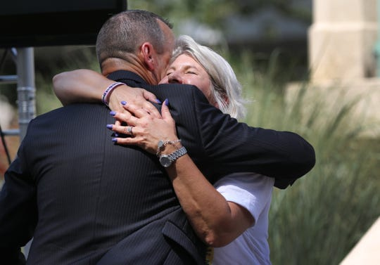 Katie Renfrow, mother of Samuel Gillman who died at 24 of an overdose, hugs Tom Fallon, investigative commander of the Hamilton County Heroin Task Force as he receives an Angel Award last summer at Washington Park on Overdose Awareness Day.