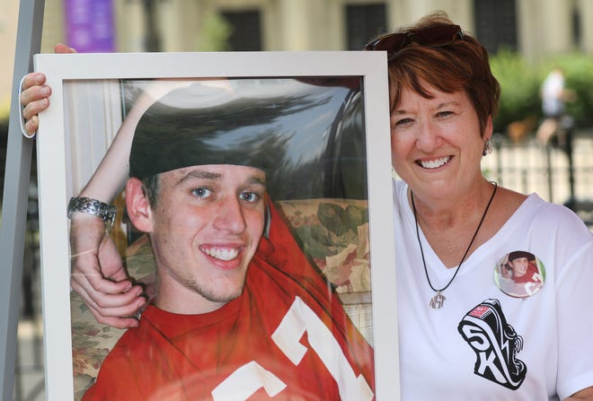Holly Specht, of Ft. Thomas, holds up a photo of her son, Nicholas, 30, who overdosed and died August 5, 2013. Shortly after his death, the family started NKY Hates Heroin. Holly was taking part in the Overdose Awareness Day at Washington Park. The international event raises awareness of overdose and hopes to reduce the stigma of addiction.