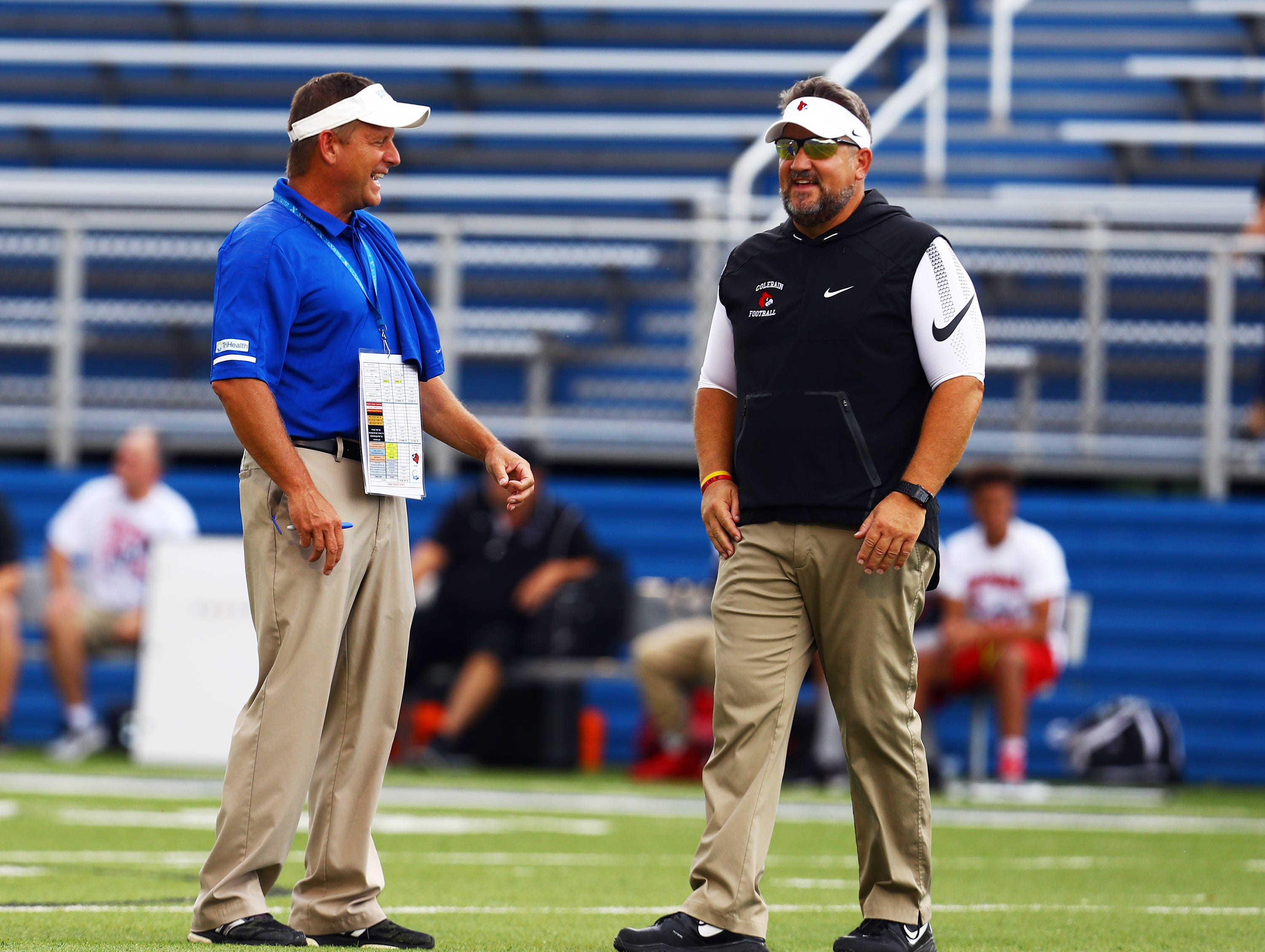 Saint Xavier Head Coach Steve Specht [left] and Colerain Head Coach Tom Bolden meet during pre game activities before the game between the Colerain Cardinals and the Saint Xavier Bombers at Saint Xavier High School.