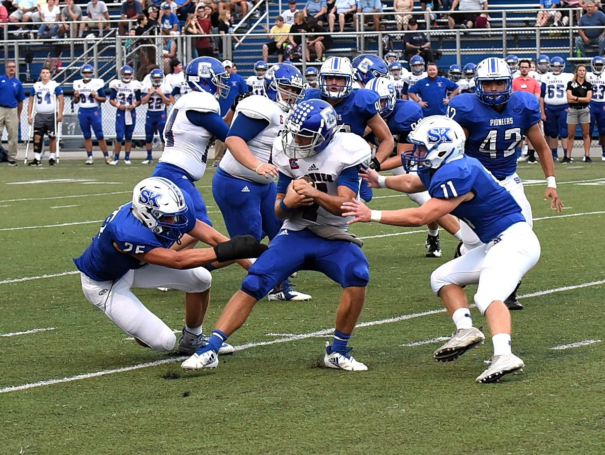 Jared Hicks (7) of Conner is sandwiched between Simon Kenton defenders after picking up first down yardage, August, 31, 2018.