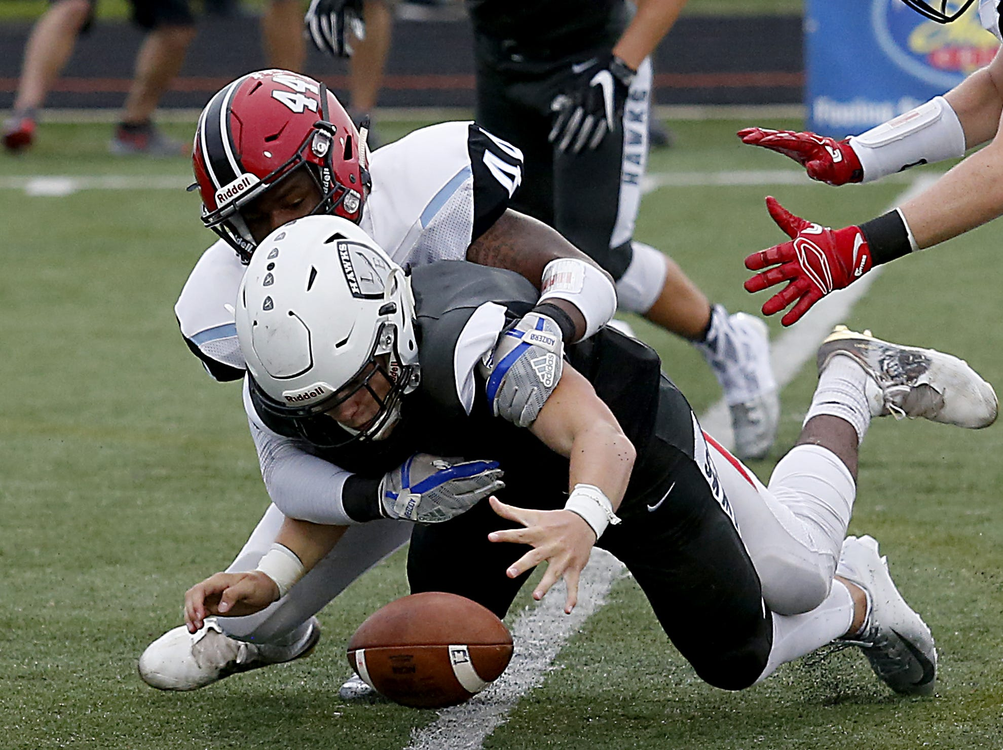 Lakota East quarterback Sean Church manages to fall on his fumble after a hit from Kings linebacker Treshawn Fisher during their Skyline Chili Crosstown Showdown game at Lakota East Friday, August 31, 2018.