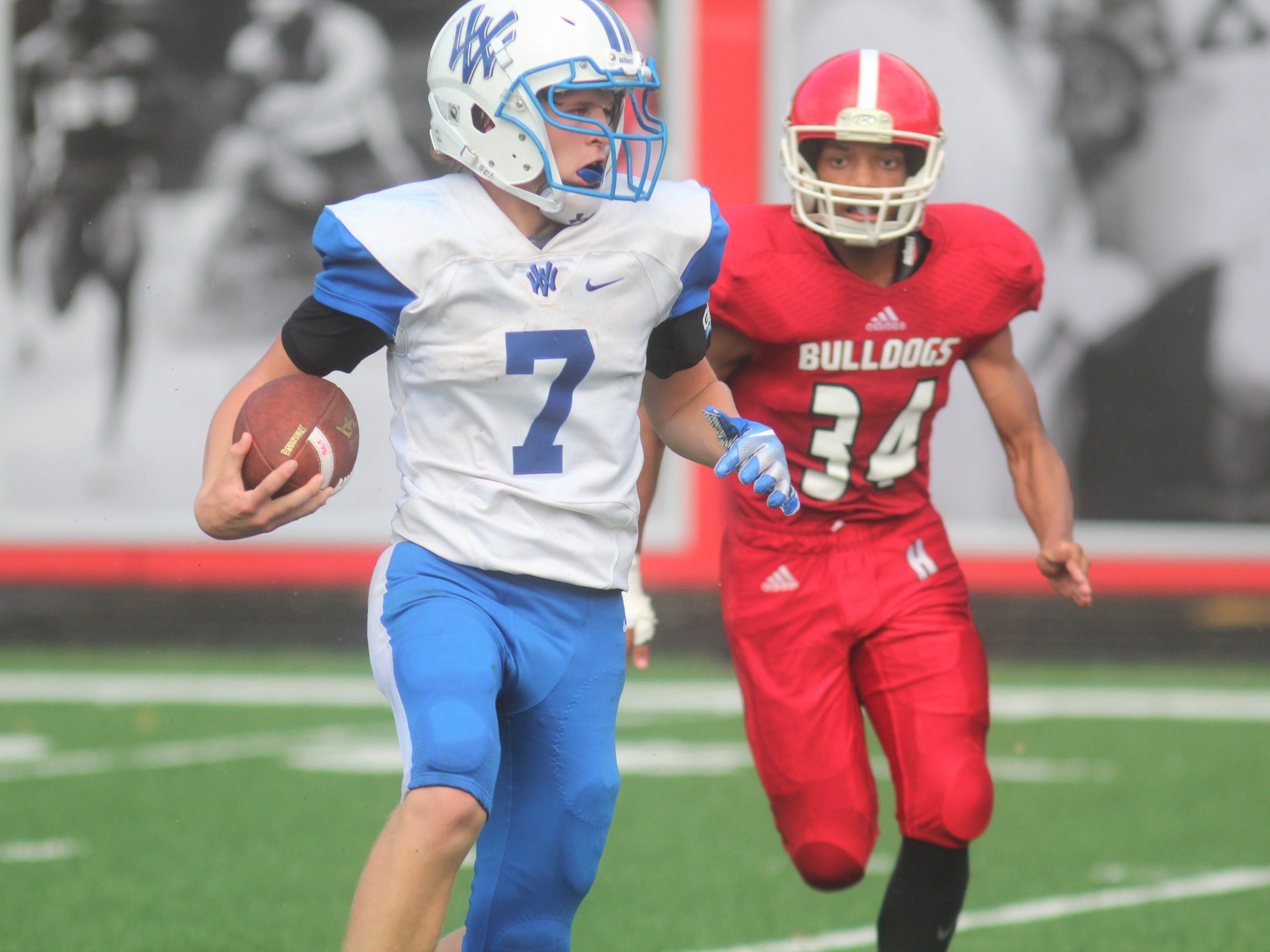 Walton-Verona senior QB Garrett Jones tries to elude Holmes junior Marcus Elmer during Walton-Verona's 48-0 win over Holmes September 1, 2018 at Holmes High School, Covington KY. The game concluded on Saturday morning after being suspended at halftime because of weather.