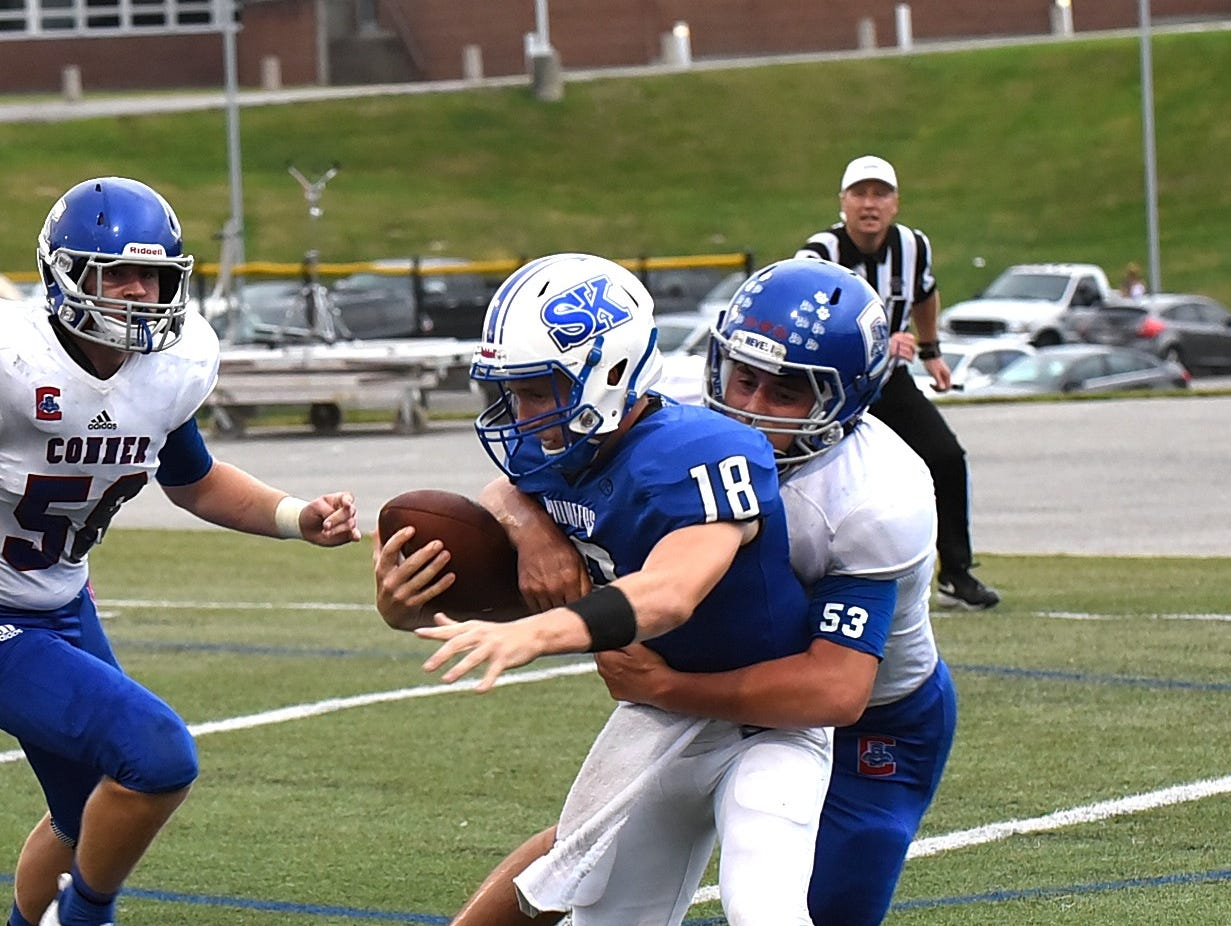 Simon Kenton auarterback Caleb Farfsing is sacked by Conner's Zane Cahill (53) but avoids being tackled in the endzone for a safety, August 31, 2018.