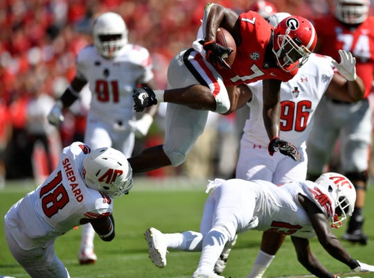 Georgia running back D'Andre Swift (7) leaps over Austin Peay defensive back Kordell Jackson (13) and Austin Peay linebacker Elijah Shepard (18) during the first half of an NCAA college football game, Saturday, Sept. 1, 2018, in Athens, Ga.