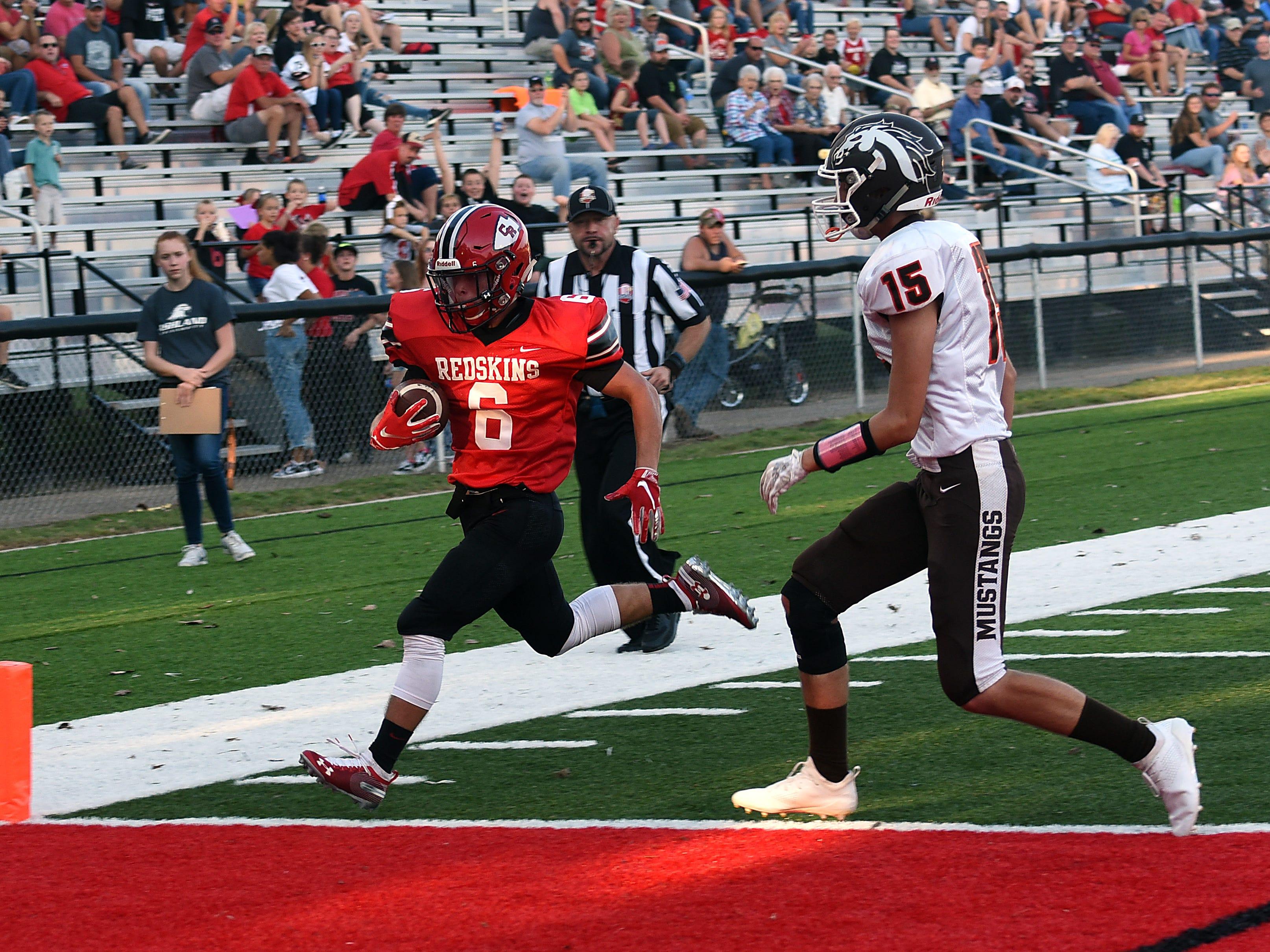 Coshcoton senior Andrew Kitten outruns Claymont defender Derek Moreland to score the first touchdown during Friday night's home opener. Coshocton won 42-6.