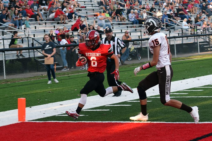 Coshcoton senior Andrew Kitten outruns Claymont defender Derek Moreland to score the first touchdown during Friday night's home opener. Coshocton won 42-6.