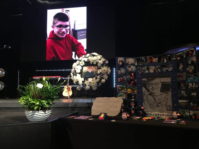 Jake Wilson's photo shows on a screen behind photos, flowers and memorabilia during a memorial Sept. 1, 2018, at Candeo Church in Cedar Falls.