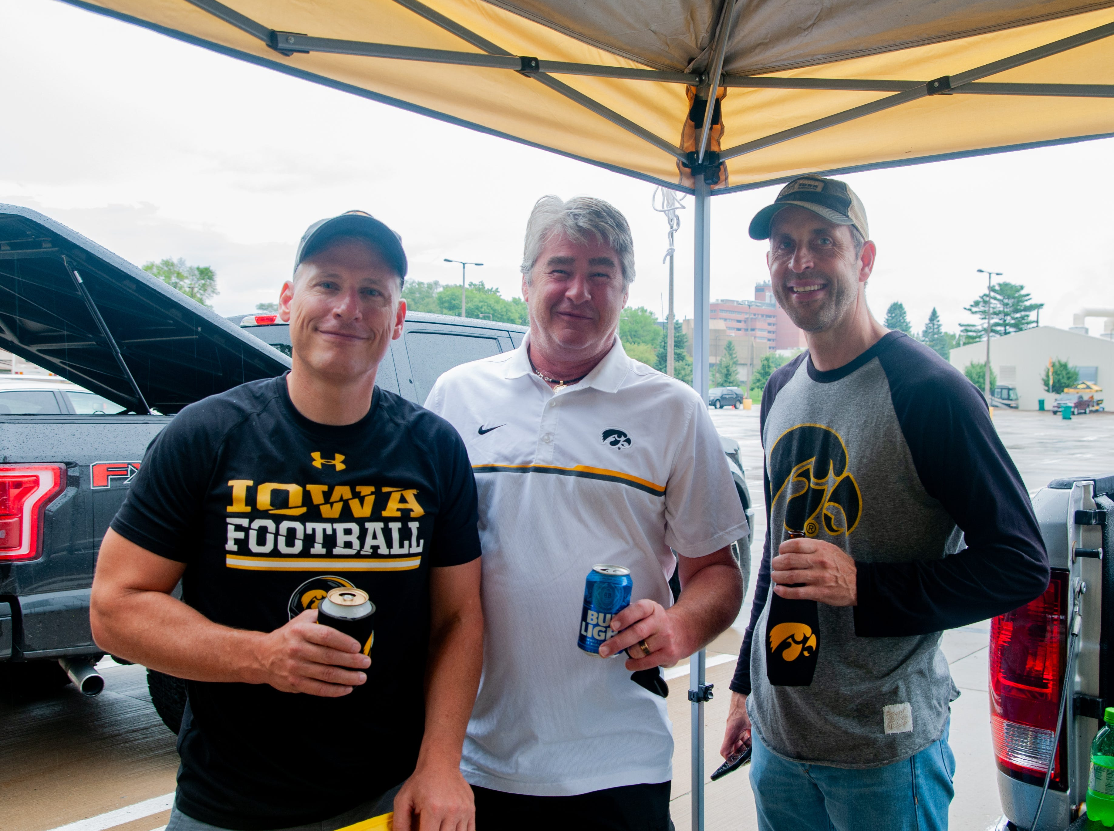 Chuck Augustine, 47, (left), Tim Tierney, 58, and John Tentinger, 46, Saturday, Sept. 1, 2018, while tailgating before the Iowa game against Northern Illinois in Iowa City.