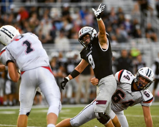 Urbandale Quarterback J.D. Colby (1) fires off a pass under while under pressure from Ankeny Centennial Defender Kyle Gustofson (8) on Friday, August 31, 2018 during a football game between the Ankeny Centennial Jaguars and the Urbandale J-Hawks at Northview Middle School.