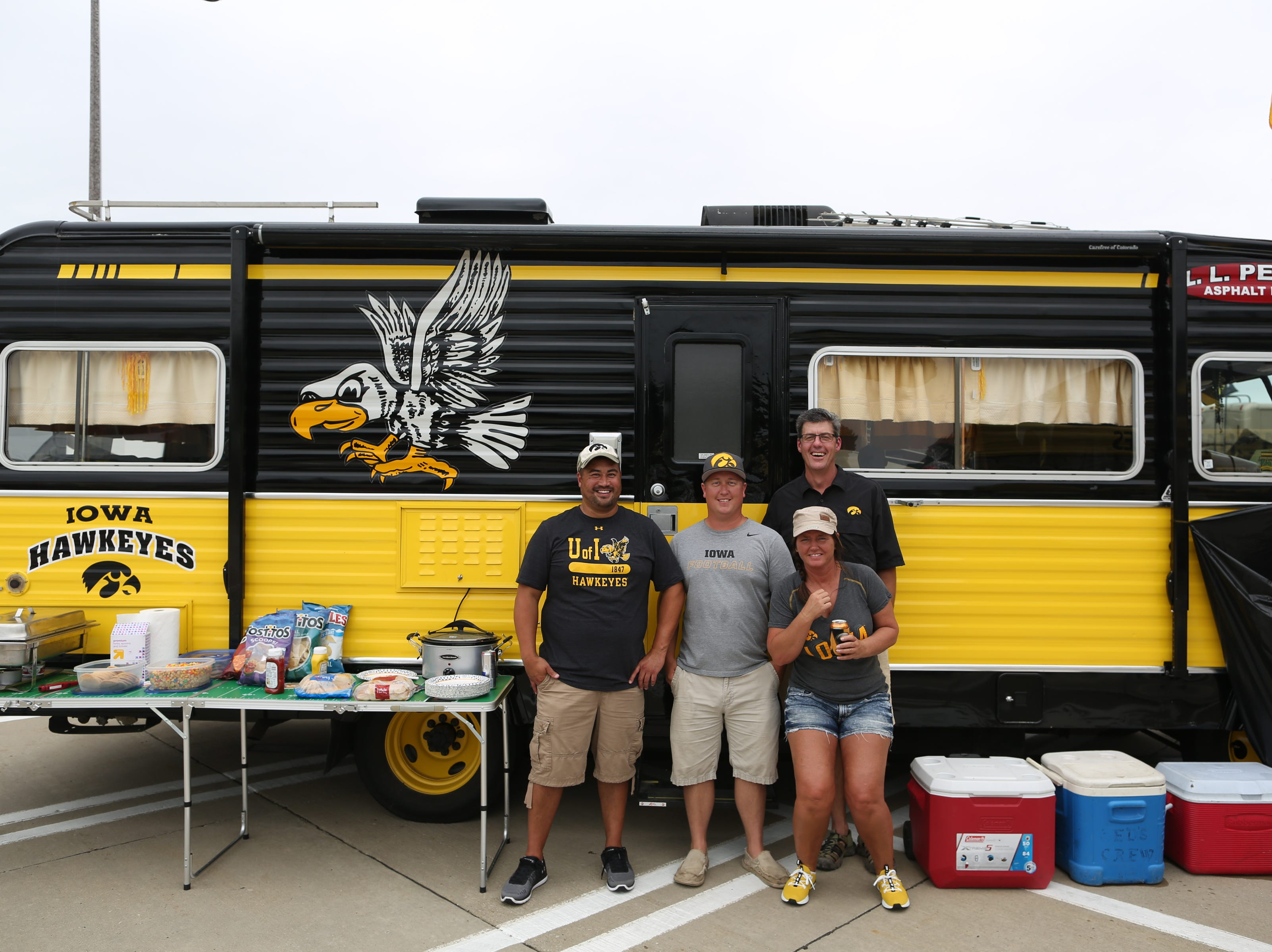 Iowa fans from North Liberty pose for a photo with their van before the Hawkeyes' game against Northern Illinois at Kinnick Stadium on Satuday, Sept. 1, 2018.
