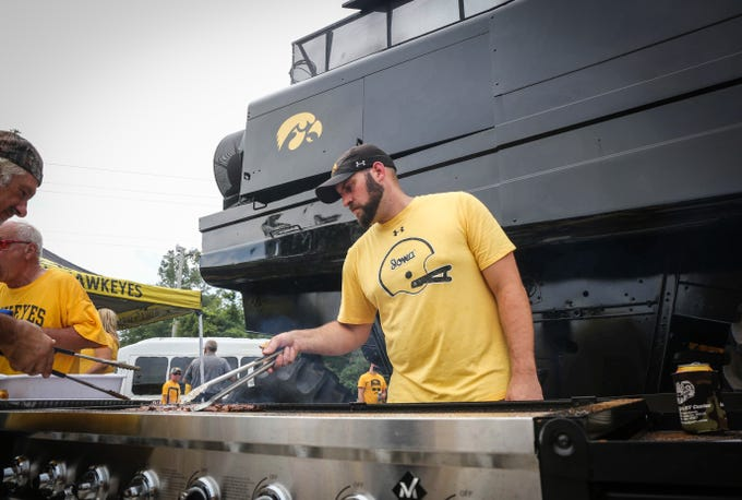 Chris Ford of Newton flips steaks from a grill while tailgating prior to kickoff against Northern Illinois on Saturday, Sept. 1, 2018, in Iowa City.
