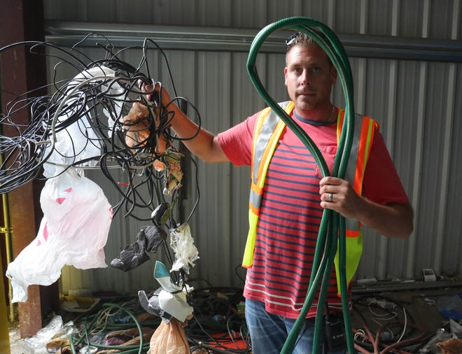 Lucas Dean, a supervisor at the SOCRRA MRF facility in Troy, with a hose and cables pulled from the material pile that can't be recycled on Thursday, August 30, 2018.