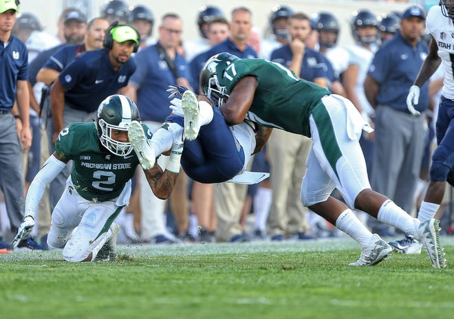 Utah State receiver Jalen Greene is upended by MSU linebacker Tyriq Thompson (17) and cornerback Justin Layne (2) during the first quarter.