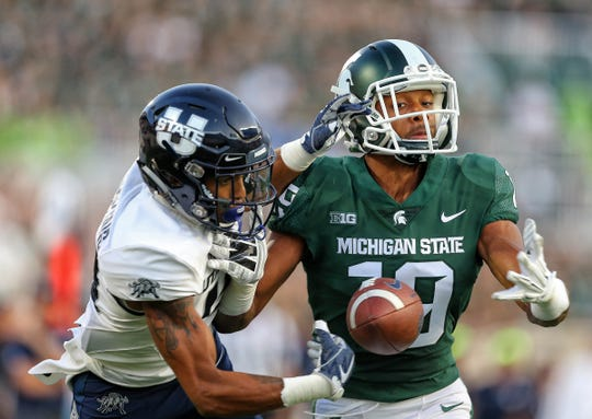 Utah State receiver Deven Thompkins battles for the ball against Michigan State cornerback Josh Butler during the first half at Spartan Stadium on Friday, Aug. 31, 2018.