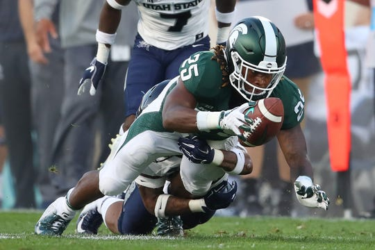 Michigan State's Darrell Stewart Jr. dives for a first down in the first half vs. Utah State at Spartan Stadium on Aug. 31, 2018 in East Lansing.