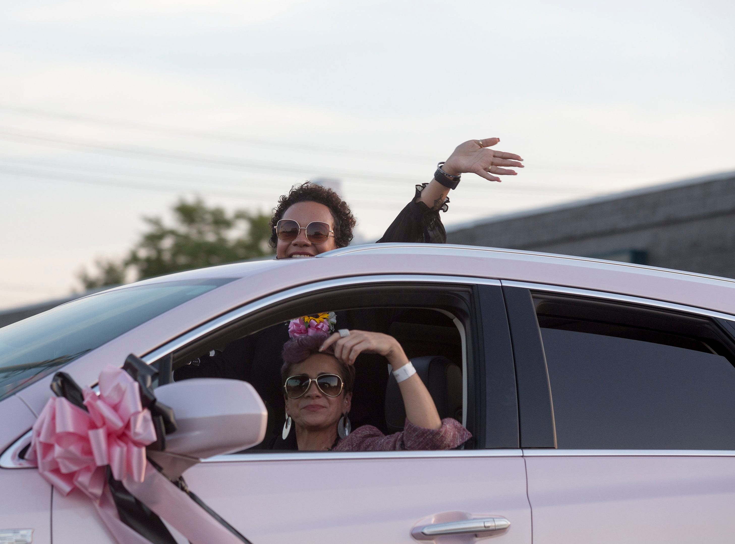 Women wave from a pink Cadillac as they escort the hearse carrying Aretha Franklin down Seven Mile Road from Greater Grace Temple to be laid to rest at Woodlawn Cemetery on Friday, Sept. 31, 2018 in Detroit.