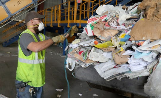 Pete Casaina, a front loader driver at the SOCRRA MRF facility in Troy, had to stop loading to remove hose and plastic found in the material pile on Thursday, August 30, 2018.