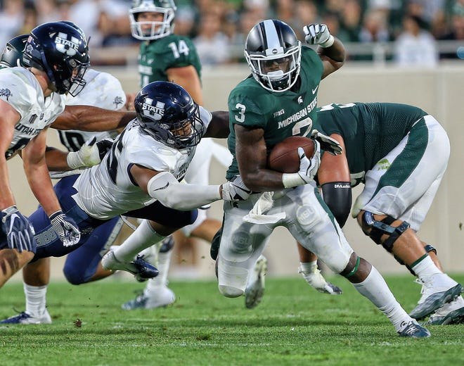 Michigan State running back LJ Scott breaks the tackle of Utah State defensive end Adewale Adeoye during the first half Friday, Aug. 31, 2018 at Spartan Stadium.