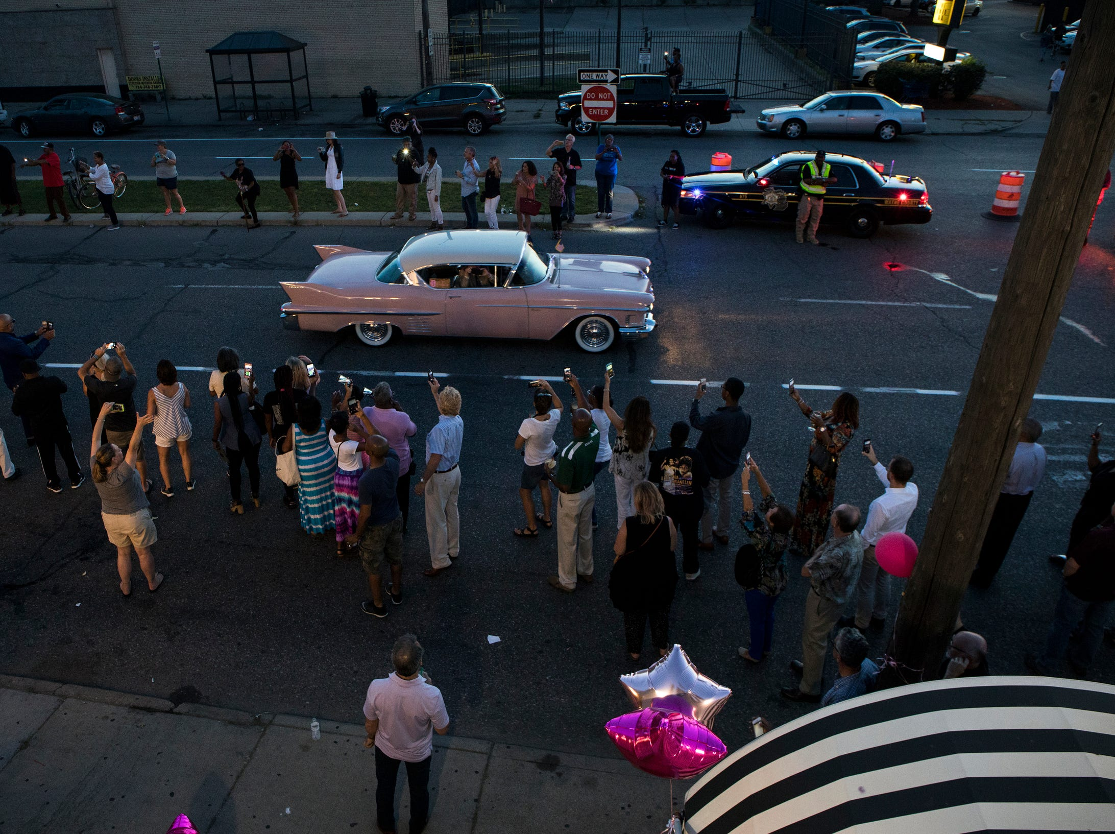 Crowds cheer as pink Cadillacs lead the funeral procession for Aretha Franklin on Livernois Avenue in Detroit, Mich., Friday, August 31, 2018.