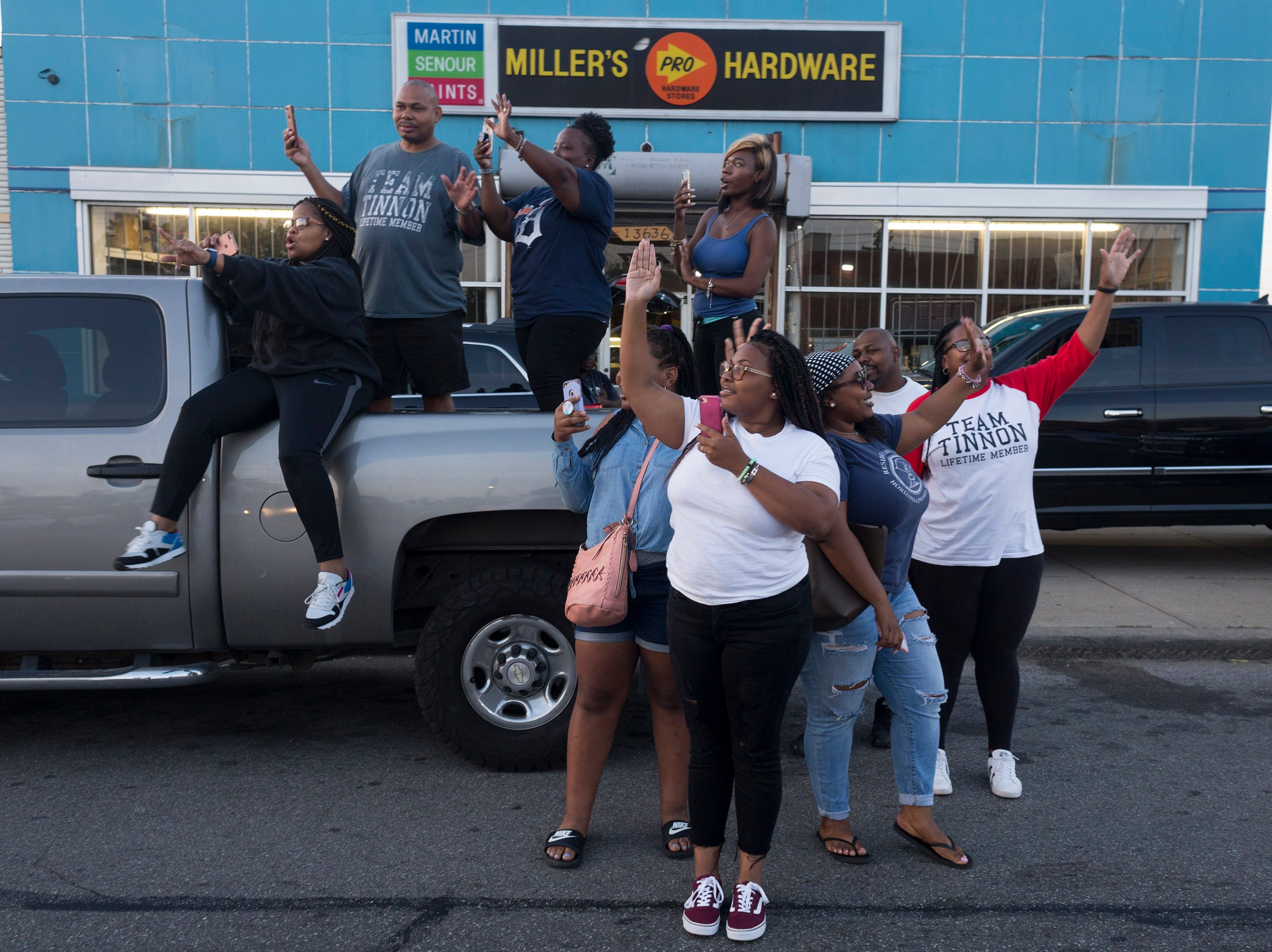 Dozens of people line Seven Mile Road waving to pink Cadillacs as they wait for the hearse carrying Aretha Franklin from Greater Grace Temple to be laid to rest at Woodlawn Cemetery on Friday, Sept. 31, 2018 in Detroit.