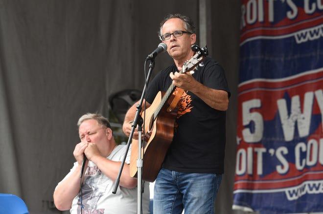 Mike Ward memainkan gitarnya dan bernyanyi di depan banyak orang di Arts, Beats, and Eats in Royal Oak pada tahun 2018. Dia bagian dari line up virtual tahun ini.