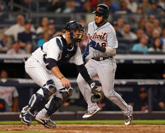 Dawel Lugo (18) of the Detroit Tigers scores on a triple by Jim Adduci (37) as catcher Austin Romine (28) of the New York Yankees waits for the throw during the fifth inning Friday. The Yankees rallied in the eighth to win 7-5.