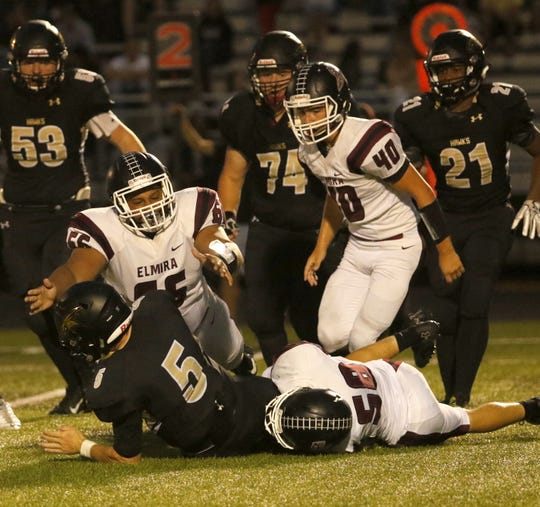Corning quarterback Blake VanWoert is tackled by Thompson Miller (58) of Elmira as Jeremiah Cheatham (66) and Lucas Allen (40) of the Express close in on the play Aug. 31, 2018 at Corning Memorial Stadium.