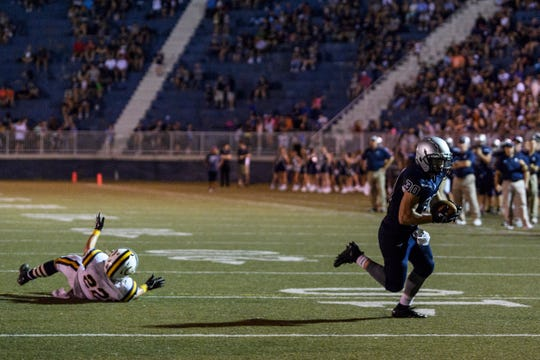 Reitz's Alex Mitchell (30) runs into the endzone after dodging a tackle attempt bye Castle's Cooper Forshee (22) in the fourth quarter at the Reitz Bowl in Evansville, Ind., Friday, Aug. 31, 2018. The Panthers secured the football program's 700th win by defeating the Knights 38-21.