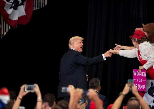 President Donald Trump shakes hands as he exits the stage after his campaign rally at the Ford Center in Evansville, Ind., Thursday night.