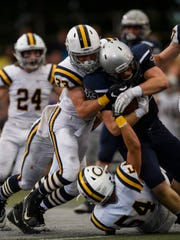 Castle's Adam Harpenau (33) and Ethan Houston (54) tackle Reitz's Carter Schnarr (33) in the first quarter of Reitz's 38-21 victory over Castle, giving the Panthers' win No. 700 in school history.